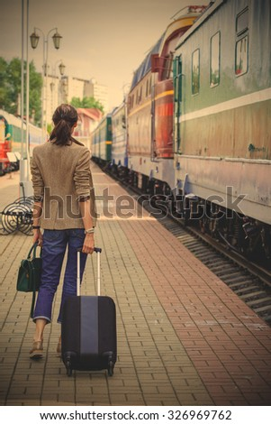 woman with luggage walking on the platform along the passenger train. returning from vacation. instagram image filter retro style - stock photo