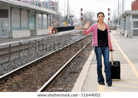 woman with luggage waving at train station