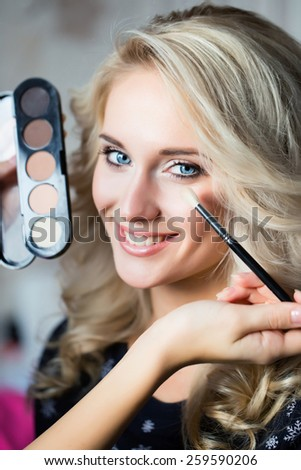 Woman with make up brush and eye shadows palette - stock photo