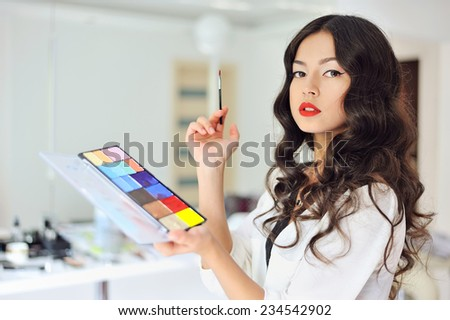 Woman with make up brush and palette - stock photo