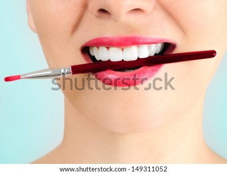 Woman with makeup brush on blue background