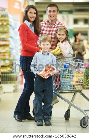 woman with man and child with chopping cart during shopping at vegetable supermarket