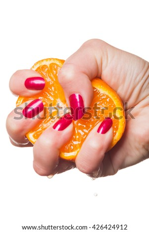 Woman with manicured red nails holding a halved fresh juicy orange in her hand in a close up view in a beauty and makeup concept - stock photo
