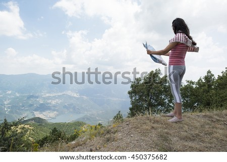Woman with map high in the mountain. View