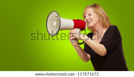 Woman with megaphone isolated on green background - stock photo