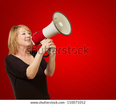 Woman with megaphone isolated on red background - stock photo