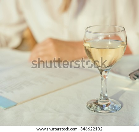 Woman with menu choosing dishes at restaurant. - stock photo