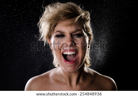 Woman with messed up makeup and hair screaming. Water particles in the air - stock photo