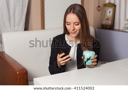 Woman with mobile phone and cup of cocktail drink - stock photo