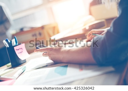 Woman with mobile phone in office. Paperwork on the table, open space. Sun glare and film effect