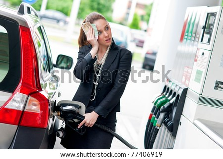 woman with money in her hand refuel car in gas station - stock photo
