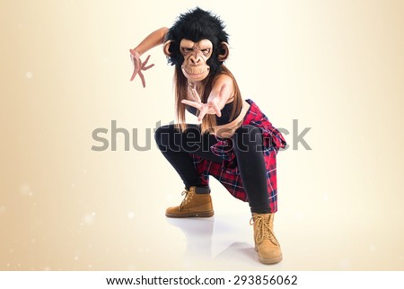 Woman with monkey mask dancing over ocher background - stock photo