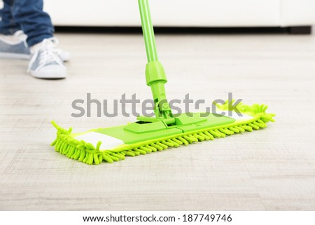 Woman with mop cleaning wooden floor from dust - stock photo
