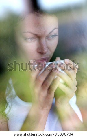woman with morning coffee looking through window - stock photo