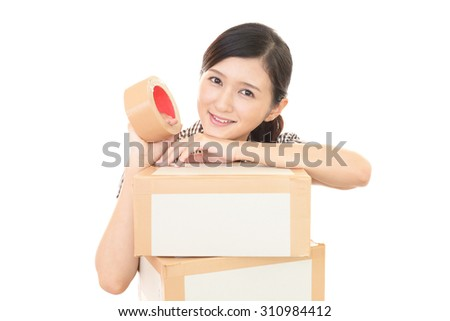 Woman with moving box in her house - stock photo