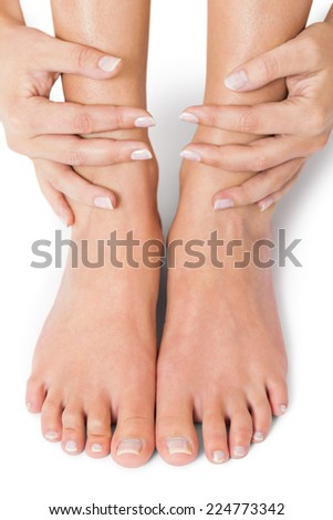 Woman with neat manicured natural nails without nail varnish showing her hands and bare feet in a beauty concept on a white background - stock photo