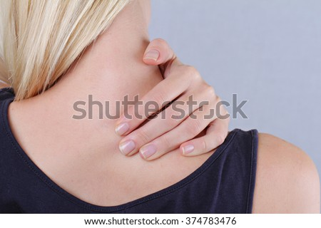 Woman with neck and back pain. Woman rubbing his painful back close up. Pain relief,  chiropractic concept - stock photo