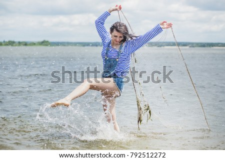 Woman with netting catches fish, girl in lake with mesh