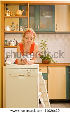 Woman with new kitchen appliance reading instructions - stock photo