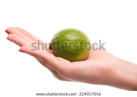 Woman with nice red polished nails showing us little green lime on her palm. Isolated on white background - stock photo