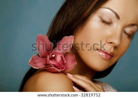 woman with orchid flower on blue background - stock photo