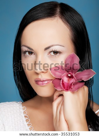 woman with orchid flower on blue background