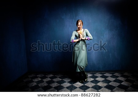 woman with orchid in hands stand in empty room, full body shot - stock photo