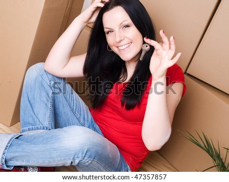 woman with package holding keys to new apartment - stock photo