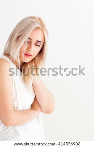 Woman with pain in neck on white background. Massage therapy of painful neck. Tired neck after long working hours. Woman relaxes the neck. - stock photo