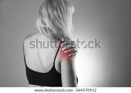 Woman with pain in shoulder. Ache in the human body on a gray background. Black and white photo with red dot