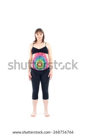 Woman with painted belly doing yoga exercise - stock photo