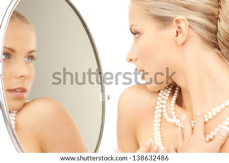 woman with pearl necklace looking in the mirror - stock photo