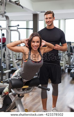 woman with personal trainer flexing muscles in gym - stock photo