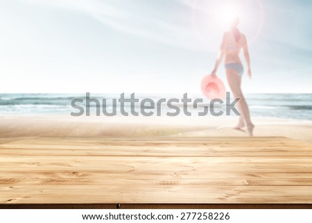 woman with pink hat on beach  and wooden top