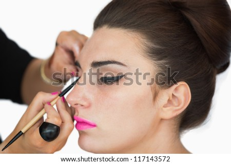 Woman with pink lips getting applied cat eyes - stock photo