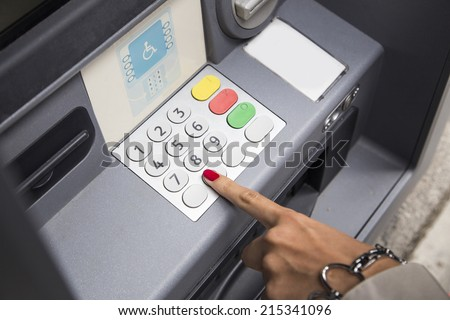 woman with polished nails withdrawing money at atm - stock photo