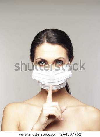 Woman with protective mask saying shh over grey background