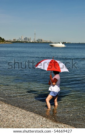 Woman with red and white umbrella looking at Toronto skyline