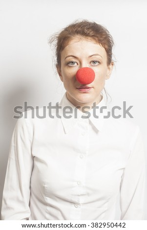 Woman with red clown nose on white background - stock photo