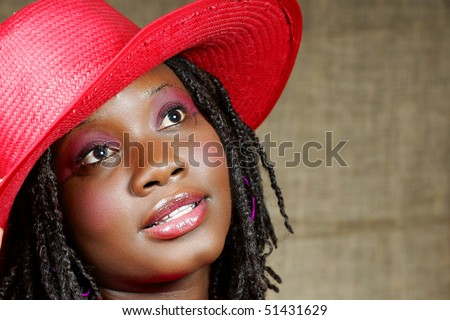 woman with red floppy hat looking up away from you - stock photo