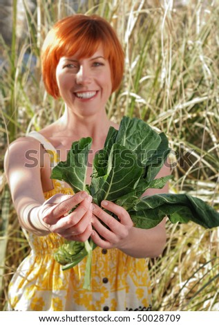 Woman with red hair holding fresh green vegetable - stock photo