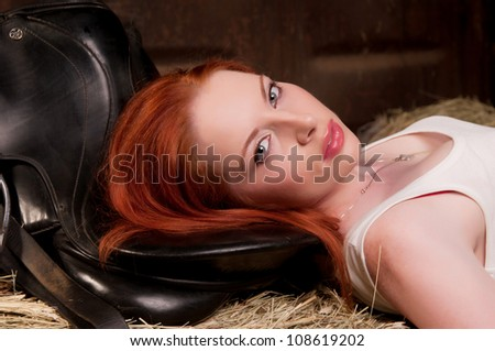 woman with red hair lying on a haystack