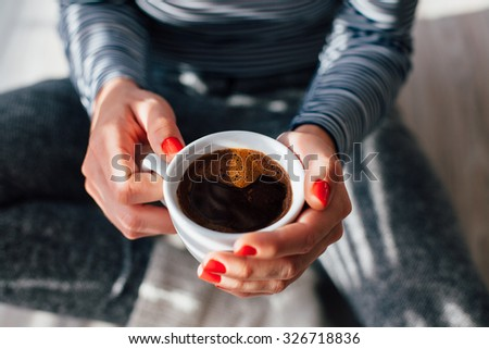 Woman with red nails sitting and holding a hot cup of coffee - stock photo