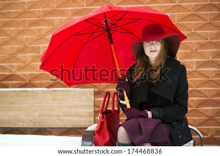 Woman with red purse and umbrella on bench - stock photo