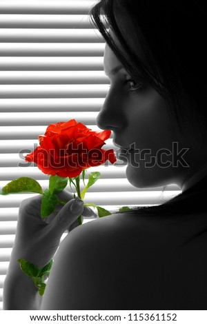 Woman with red rose - portrait - stock photo