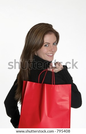 Woman with red shopping bag looking back - stock photo