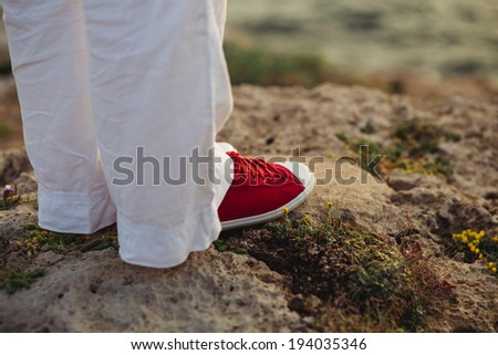 Woman with red sneakers standing on rocky beach