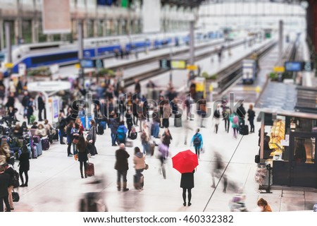 woman with red umbrella waiting at train station and blurred people in motion, solitude concept - stock photo