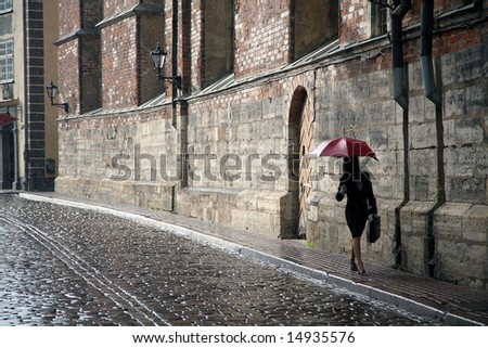 woman with red umbrella walking on the rain