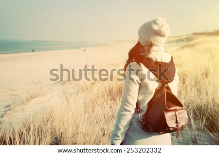 Woman with retro backpack standing on the beach, dunes and looking at the sea. Vintage mood, adventure, travel - stock photo